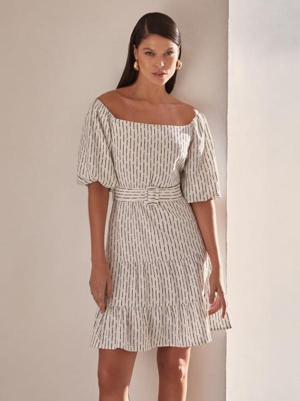 A alta do decote ombro a ombro: modelo com um vestido alfaiataria.