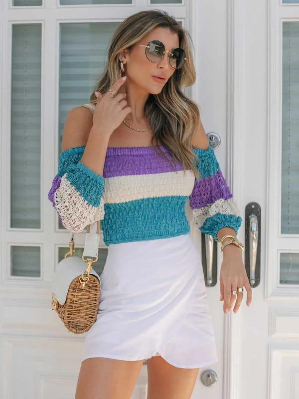 A alta do decote ombro a ombro: modelo com uma blusa cropped listrada.