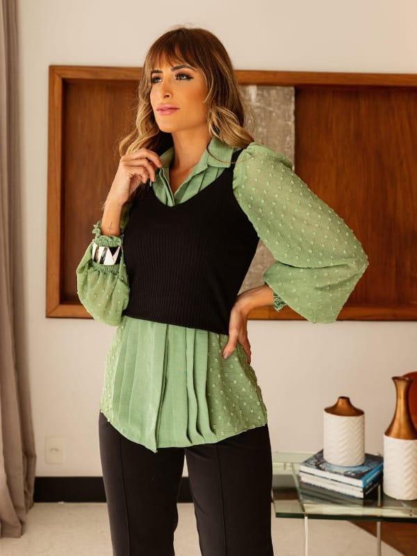 A volta das mangas bufantes: modelo usando uma camisa verde com uma blusa preta de sobreposição.