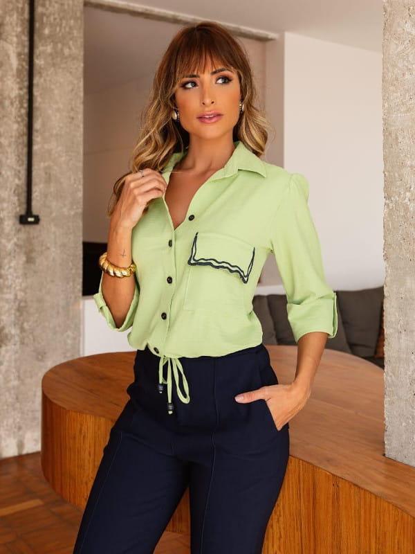 A volta das mangas bufantes: modelo usando uma camisa verde com amarração.