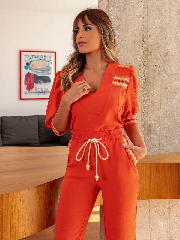 A volta das mangas bufantes: modelo usando um conjunto laranja.