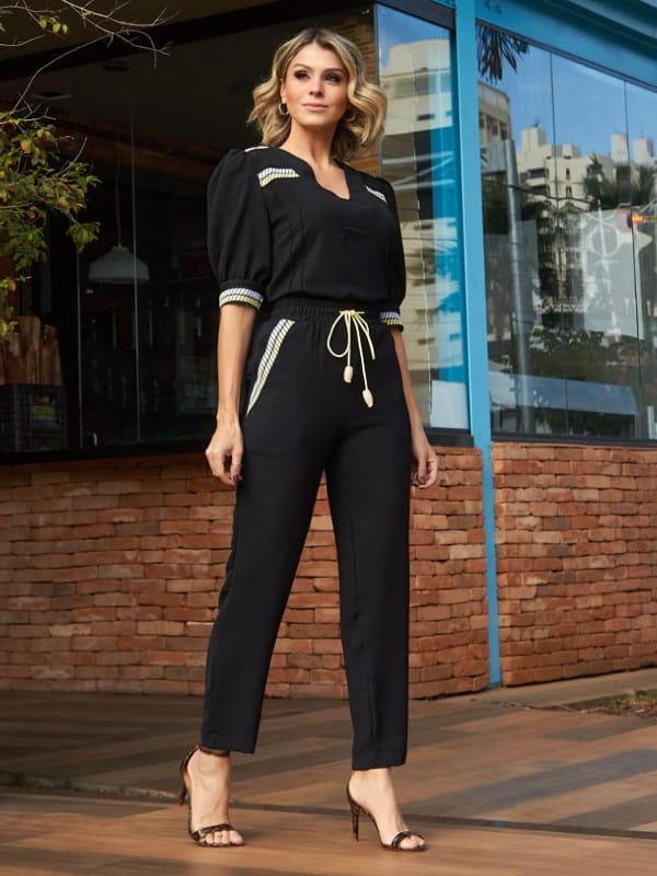 A volta das mangas bufantes: look todo preto com blusa bufante e decote V.