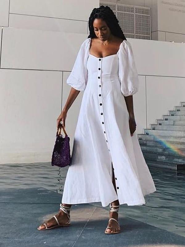 Abotoamento: saiba como usar: modelo com um vestido longo branco com botões.