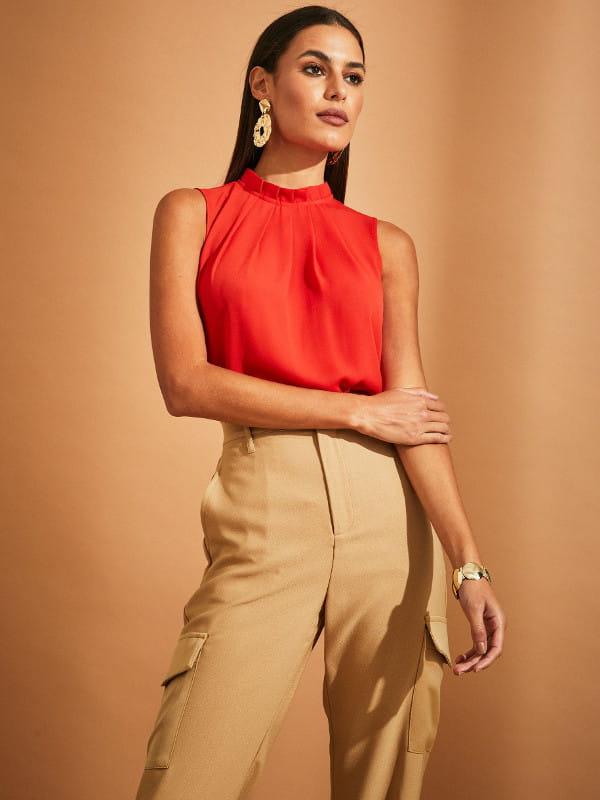 As cores do inverno 2021: modelo vestindo uma blusa regata com pregas laranja.