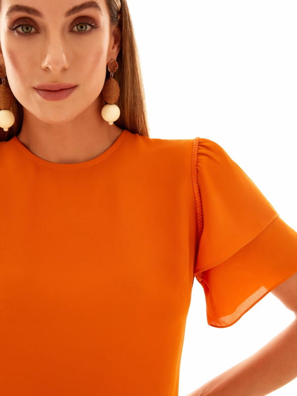 Babado: saiba como usar corretamente: mulher vestindo uma blusa laranja com babado em camadas.