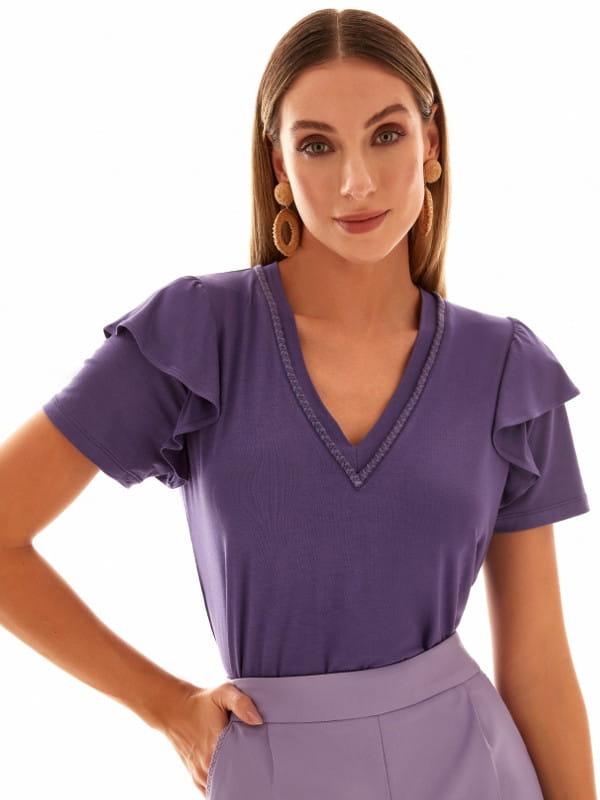 Babado: saiba como usar corretamente: mulher vestindo uma blusa lilás.