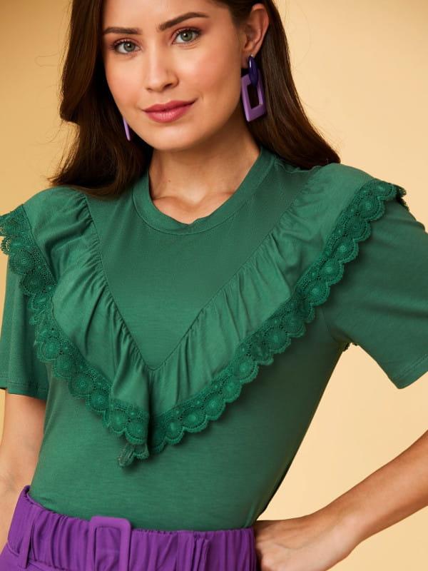 Babado: saiba como usar corretamente: mulher vestindo uma blusa verde floresta com babado e renda.