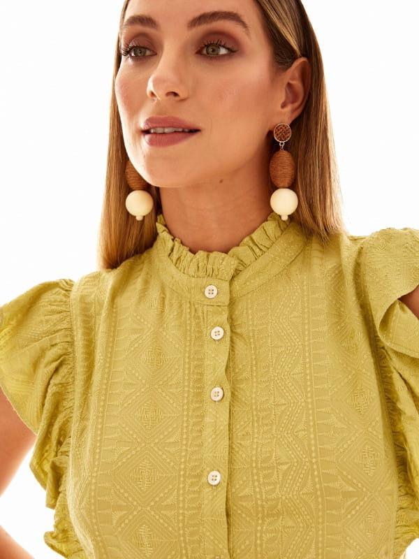 Babado: saiba como usar corretamente: mulher vestindo uma blusa verde com babado.