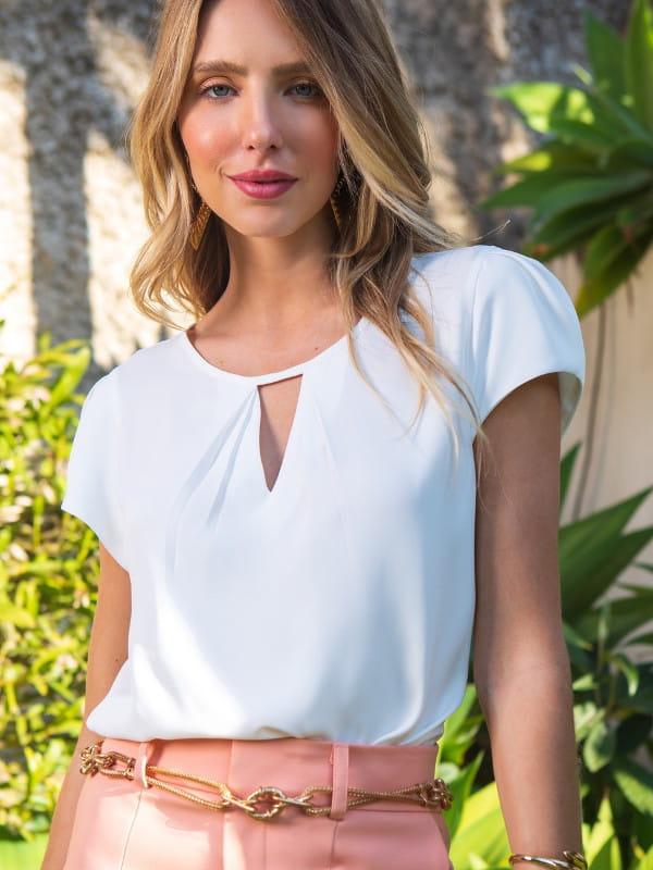 Blusa branca feminina: modelo vestindo uma blusa de crepe com decote triângulo.