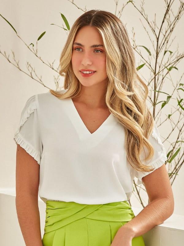 Blusa branca feminina: modelo vestindo uma blusa com decote V e manga com babados.