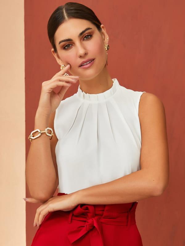 Blusa branca feminina: modelo vestindo uma regata de crepe com pregas.