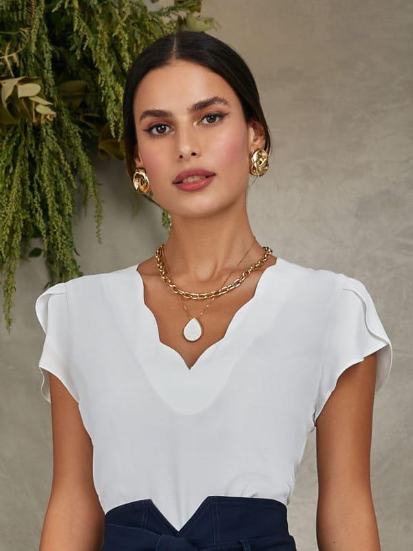 Blusa branca feminina: modelo vestindo uma blusa com decote V formato de nuvem.