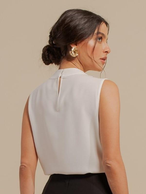 Blusa branca feminina: modelo vestindo uma blusa de crepe com pregas no ombro - costas.