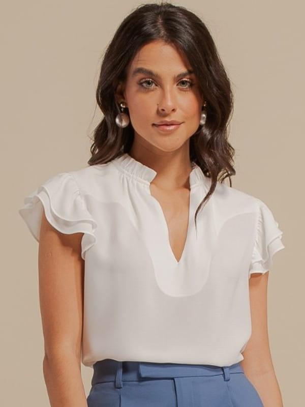 Inspire-se nos novos looks da semana: modelo vestindo uma blusa de crepe com babado duplo off white.