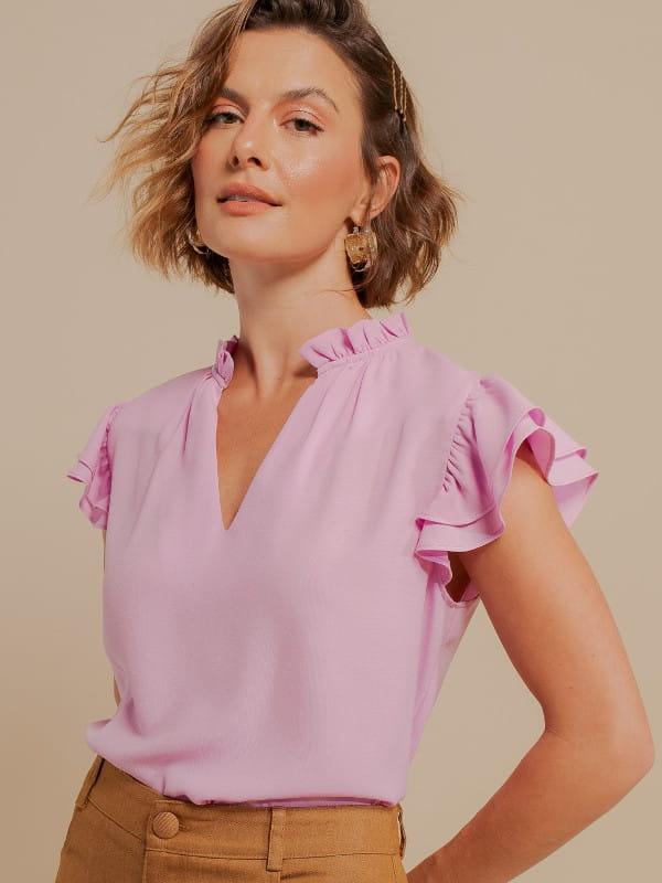 Inspire-se nos novos looks da semana: modelo vestindo uma blusa de crepe com babado duplo rosa.