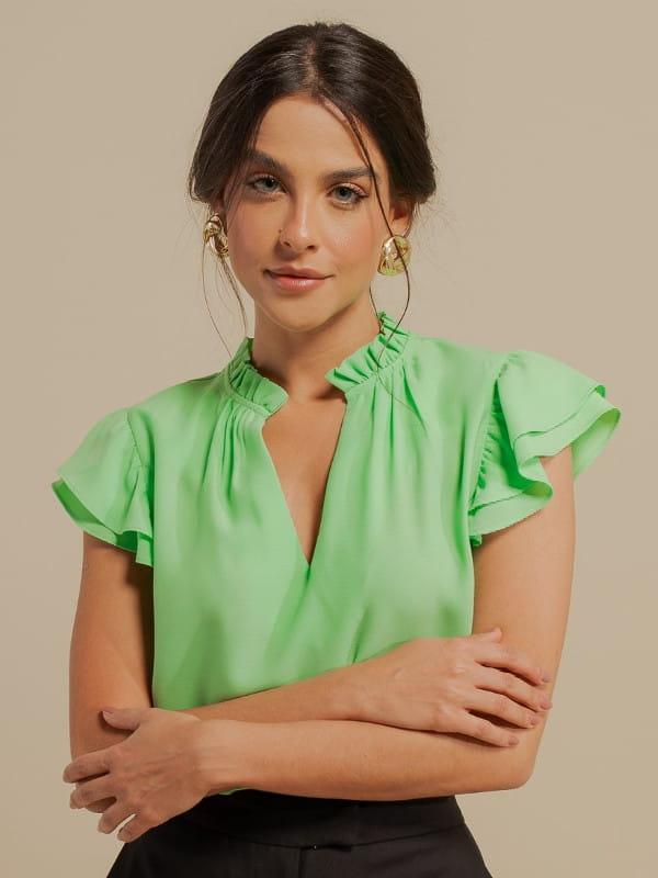 Inspire-se nos novos looks da semana: modelo vestindo uma blusa de crepe com babado duplo verde claro.
