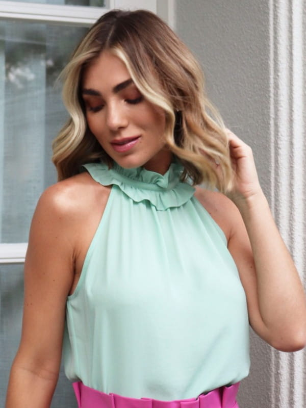 Blusa feminina de crepe: Modelo vestindo uma blusa de crepe com babado na gola verde.