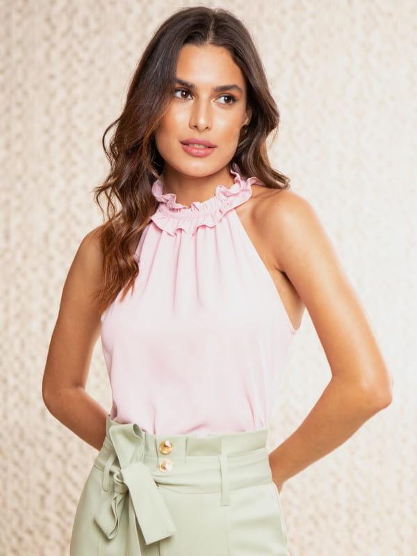 Blusa feminina de crepe: Modelo vestindo uma blusa de crepe com babado na gola rosa.