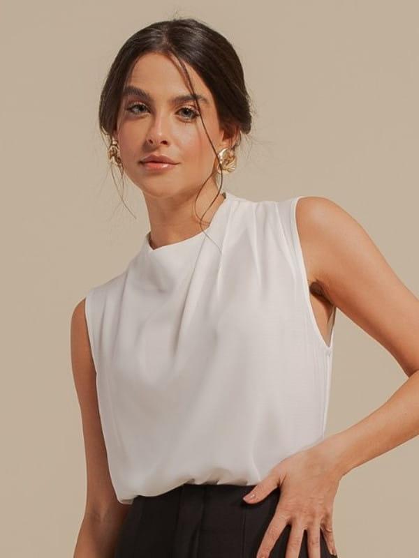 Inspire-se nos novos looks da semana: modelo vestindo uma blusa de crepe com pregas no ombro off white.