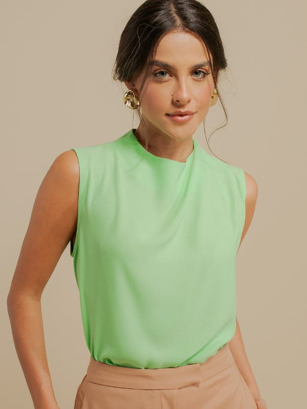 Inspire-se nos novos looks da semana: modelo vestindo uma blusa de crepe com pregas no ombro verde claro.