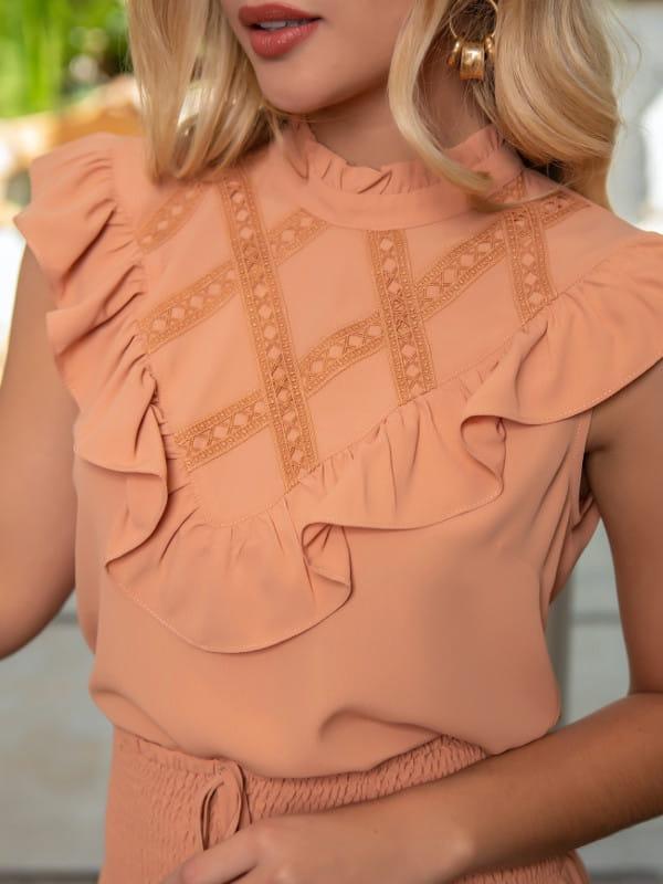 Blusa de crepe com renda: modelo vestindo uma blusa de crepe com renda na parte de cima.