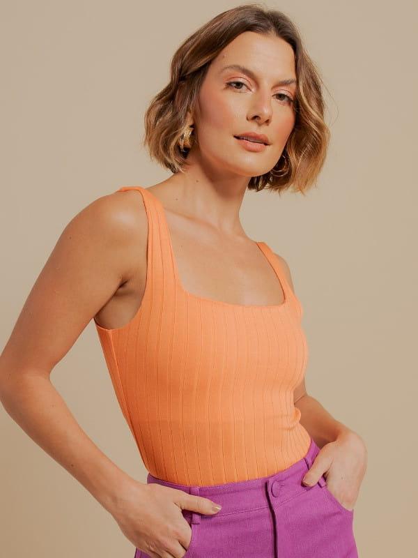Inspire-se nos novos looks da semana: modelo vestindo uma blusa de malha canelada laranja.