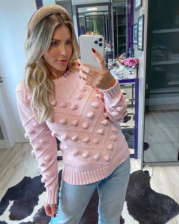 Mulher jovem vestindo blusa de tricot com detalhes em pompom.