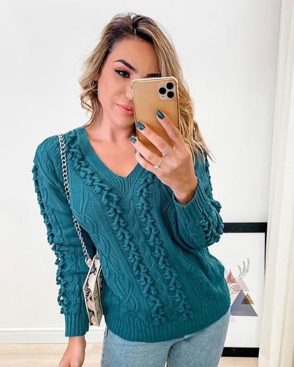 Modelo vestindo uma blusa de tricot com detalhes trançados.