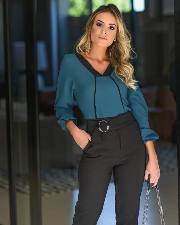 Modelo vestindo uma blusa de viscose manga comprida azul petróleo.