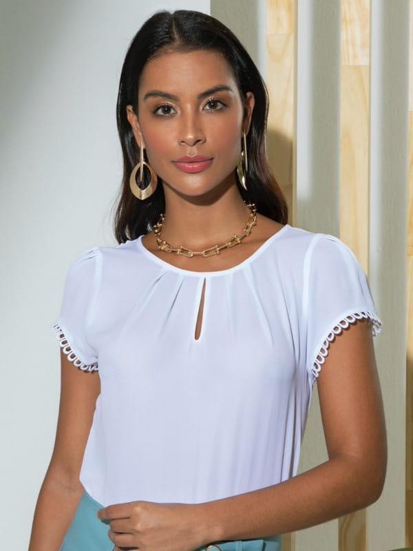 Blusa social feminina: modelo vestindo uma blusa de crepe off white com renda nas mangas.