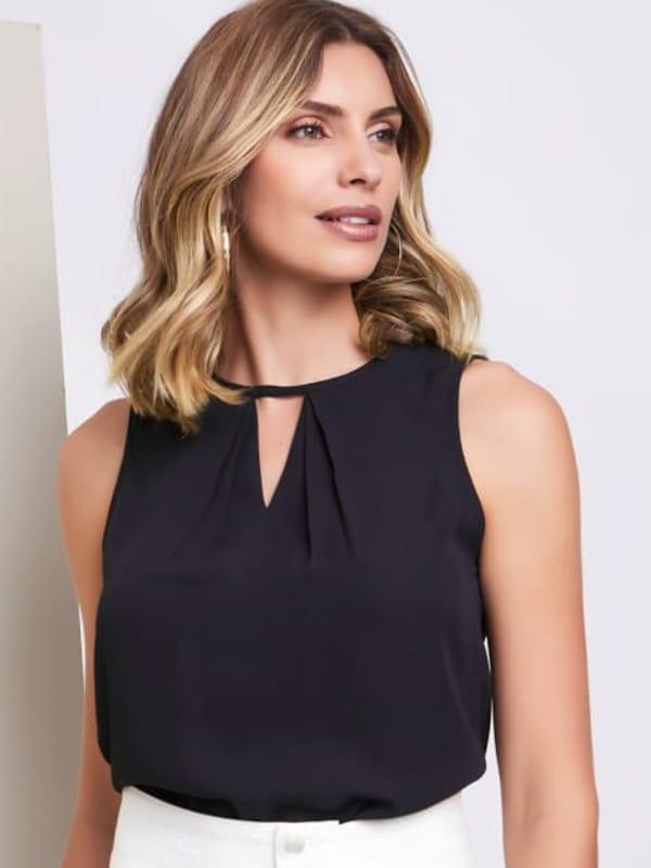 Blusa feminina social: modelo vestindo uma regata preta com decote V.