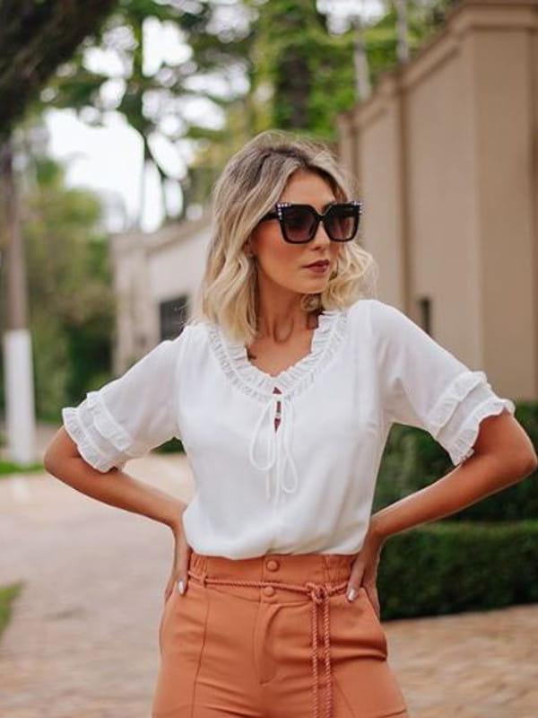 Modelo vestindo uma blusa de manga curta de crepe franzido.