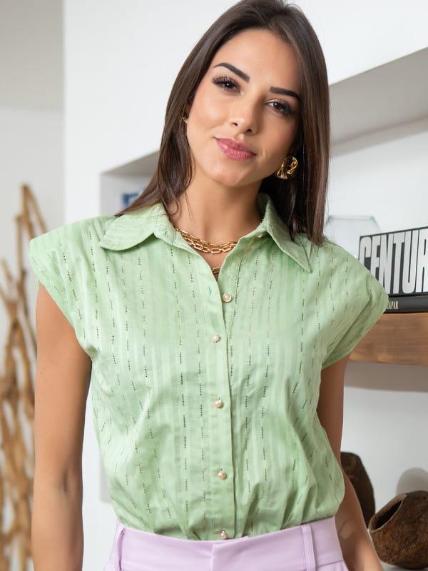 Blusa muscle tee: modelo vestindo uma blusa verde com botões.