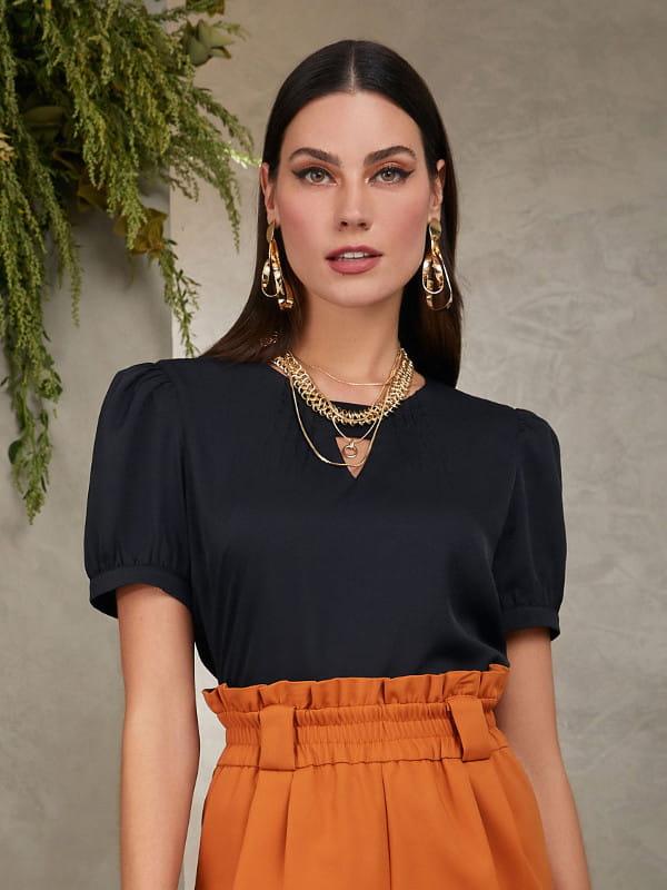 Blusa preta social feminina: modelo vestindo uma blusa de crepe com elástico no decote.