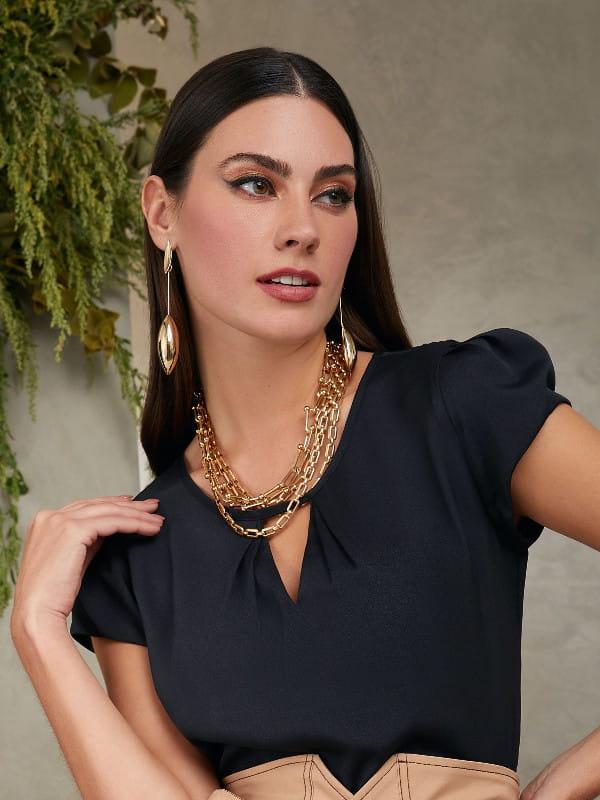Blusa preta social feminina: modelo vestindo uma blusa de crepe com decote triângulo e pregas.