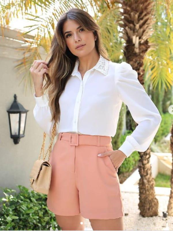 Blusa feminina social: modelo vestindo uma camisa branca com renda na gola.