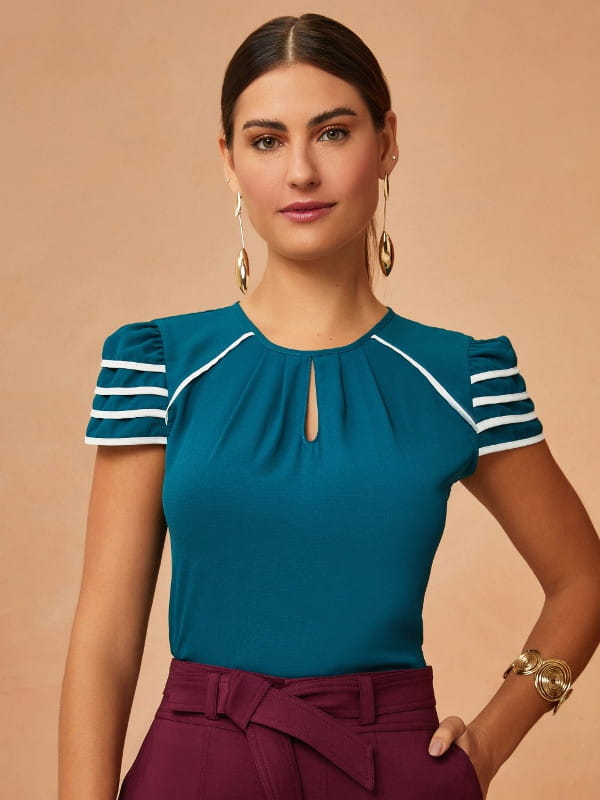 Blusa social feminina: modelo vestindo uma blusa bicolor branca e azul petróleo.