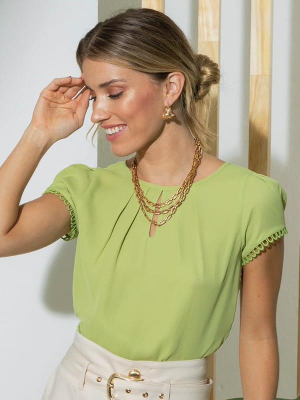 Blusa verde social feminina: modelo vestindo uma blusa de crepe com elástico no decote.