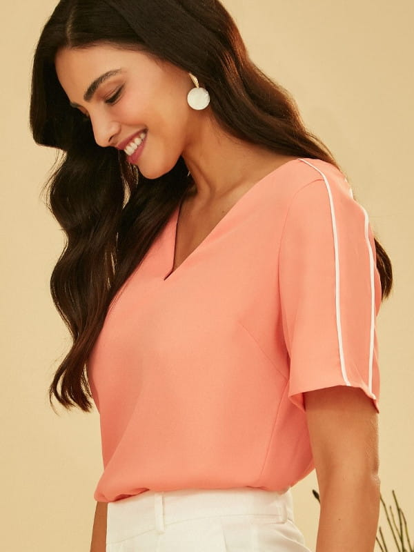 Blusas femininas da moda: modelo vestindo uma blusa de crepe decote V com detalhe na manga.
