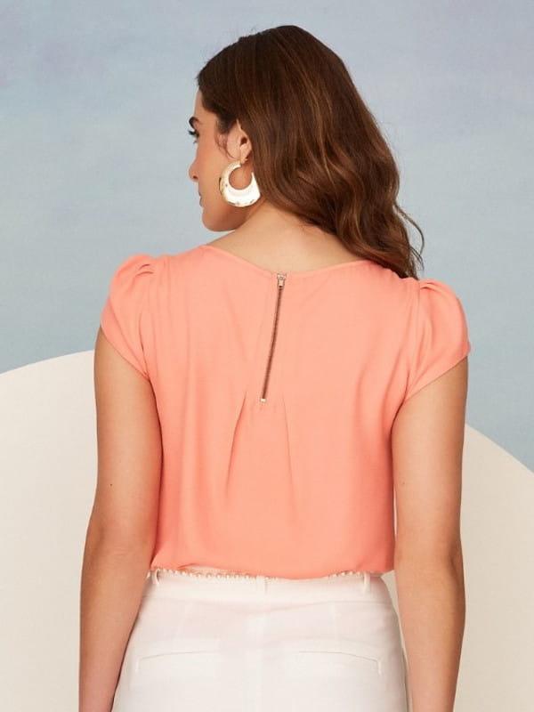 Blusas femininas da moda: modelo vestindo uma blusa de crepe laranja decote gota - costas.