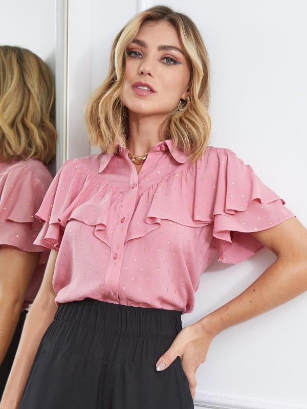 Modelo vestindo uma blusa de viscose manga curta rosé.