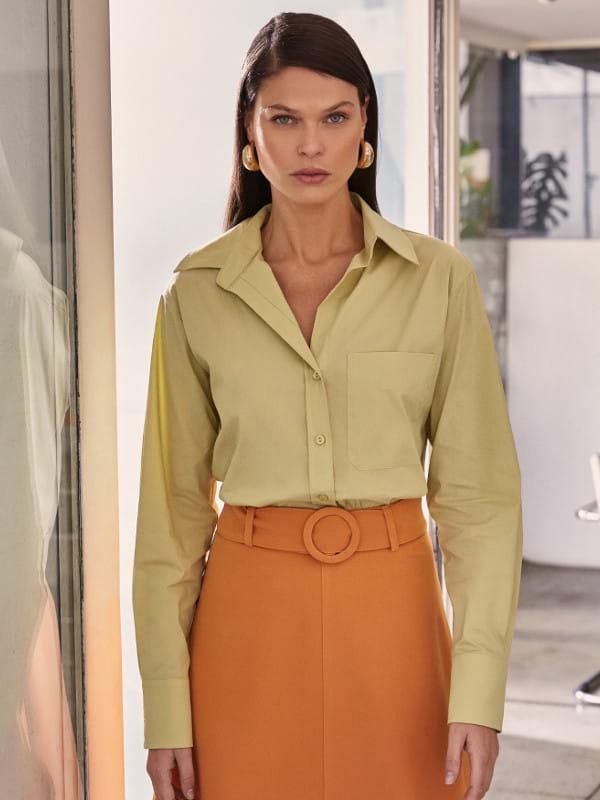 Blusas femininas da moda: modelo vestindo uma camisa tricoline básica com bolso.