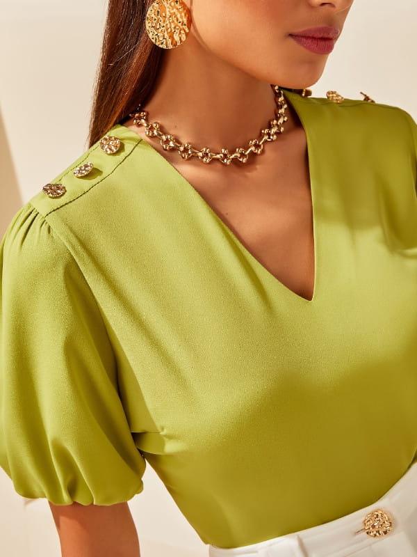 Blusas femininas delicadas: zoom em uma modelo com uma blusa de mangas bufantes.
