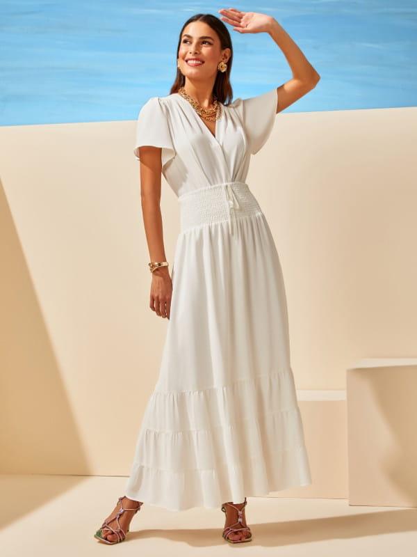 Blusas femininas delicadas: modelo descontraída vestindo uma saia com blusa off white.