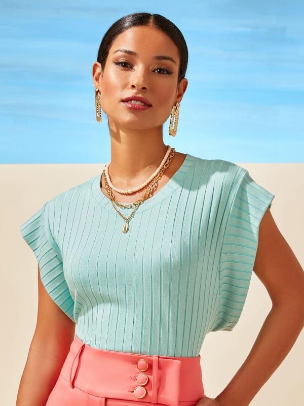 Blusas femininas delicadas: modelo vestindo uma blusa de uma cor só.