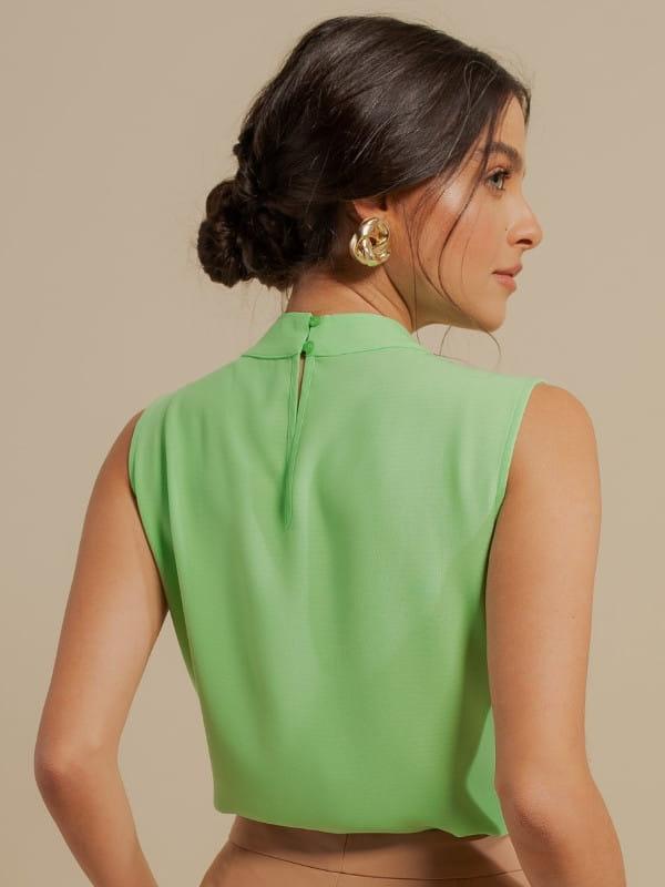 Blusas femininas para trabalhar: modelo vestindo uma blusa de crepe com pregas no ombro - costas.