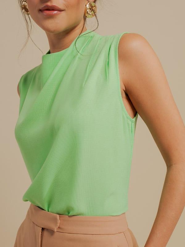 Blusas femininas para trabalhar: modelo vestindo uma blusa de crepe com pregas no ombro.