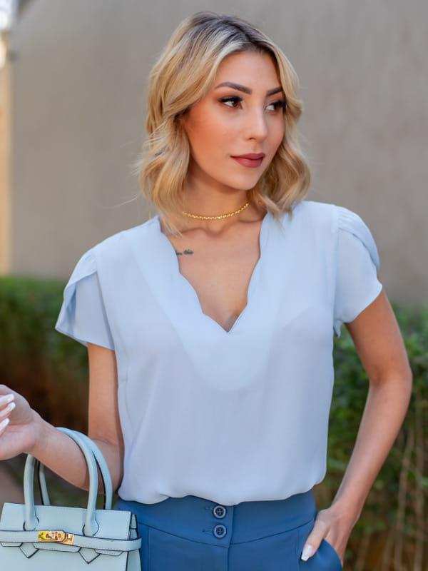 Blusas femininas para uniforme: modelo vestindo uma blusa de crepe com decote nuvem na cor azul claro.