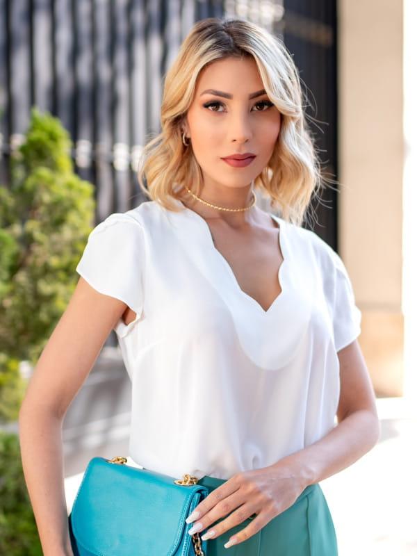 Blusas femininas para uniforme: modelo vestindo uma blusa de crepe com decote nuvem na cor branca.