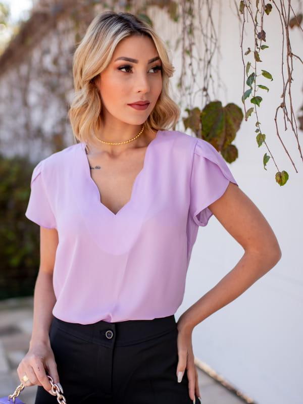 Blusas femininas para uniforme: modelo vestindo uma blusa de crepe com decote nuvem na cor lilás.